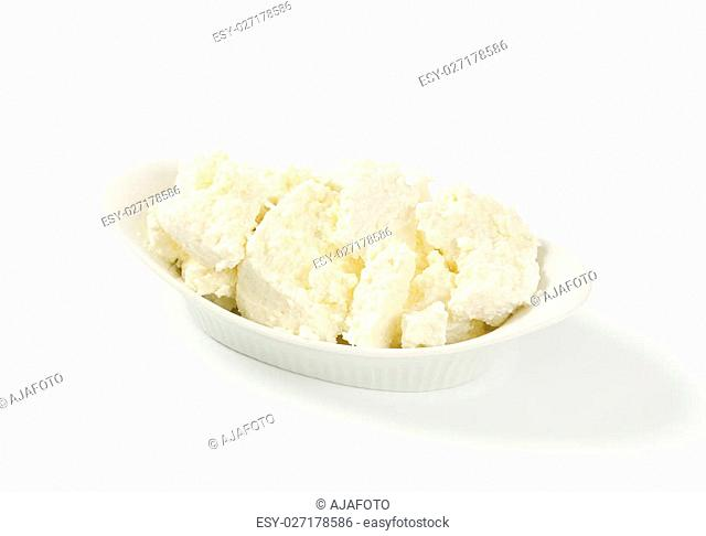 pieces of fresh curd cheese in white bowl