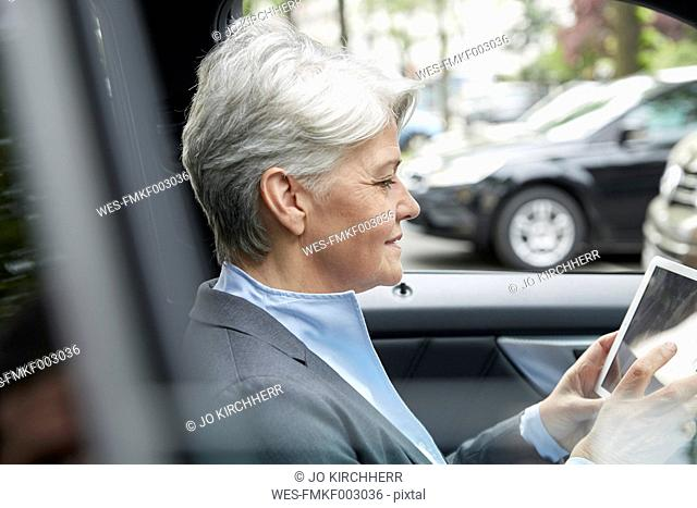 Portrait of businesswoman sitting in a car using tablet