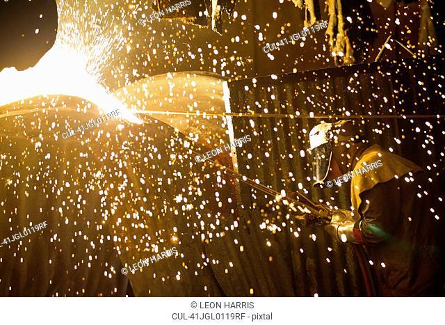 Welder at work in steel forge
