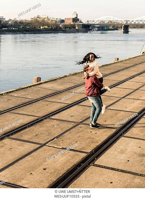 Young man lifting young laughing woman at the riverside