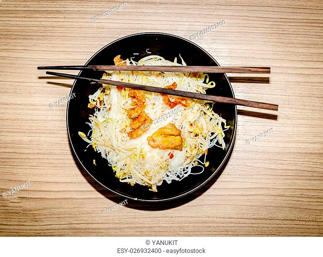white noodle and crispy pork in black bowl with wood stick tasety food on isolate