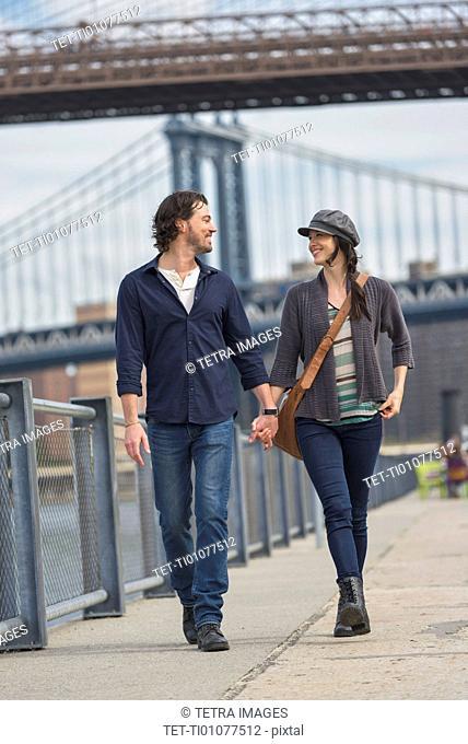 Couple walking on promenade, Brooklyn Bridge in background