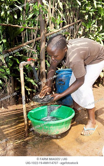 Girl washing kitchen utensils in water bowl