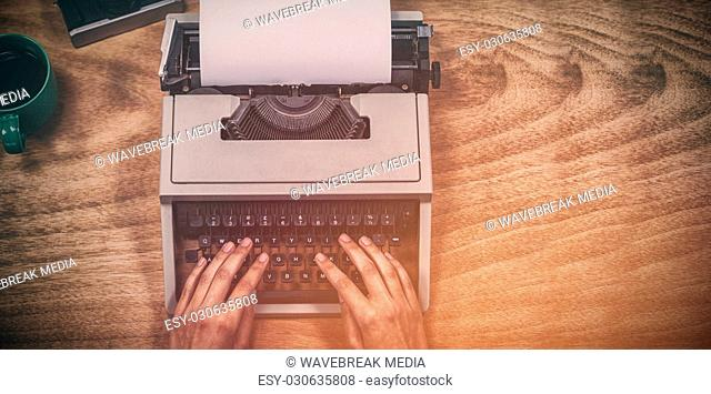 Hands of businesswoman typing on typewriter by vintage camera and coffee cup