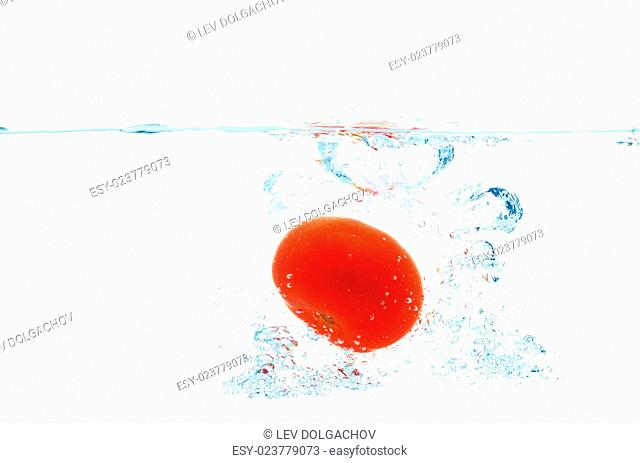 vegetables, food and healthy eating concept - close up of fresh red tomato falling or dipping in water with splash over white background