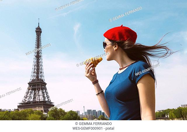 France, Paris, woman holding croissantlooking at Eiffel Tower