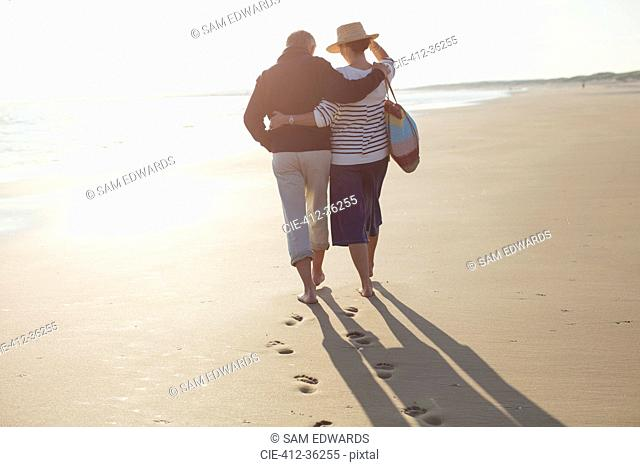 Mature couple hugging and walking on sunny beach