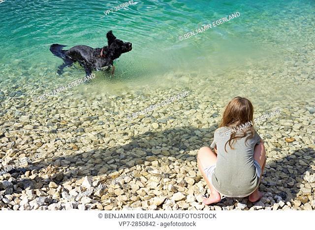 young girl enjoying summer with her dog at lake