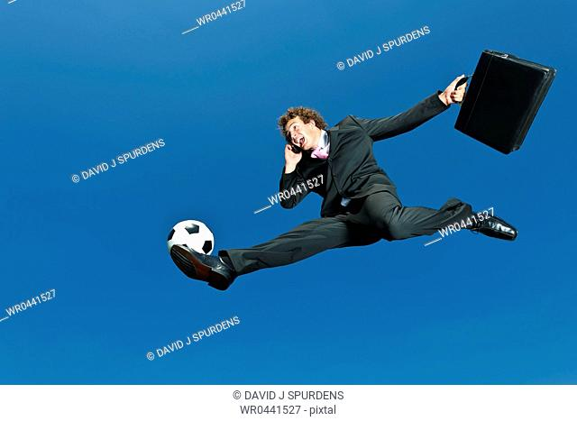 A soccer playing businessman volleys ball whilst on cellphone