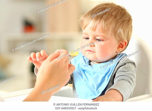 Close up of a mother hand feeding her relaxed baby sitting in a high chair