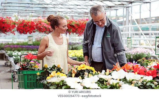 Young woman chatting to her local nursery owner about a pot plant that she is wanting to buy