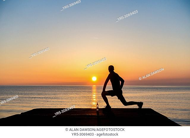 Seaton Carew, County Durham, north east England. United Kingdom. A jogger looks out over the North sea at sunrise