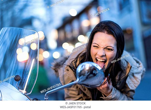 Young woman looking in wing mnirror of a motor scooter sticking her tongue out