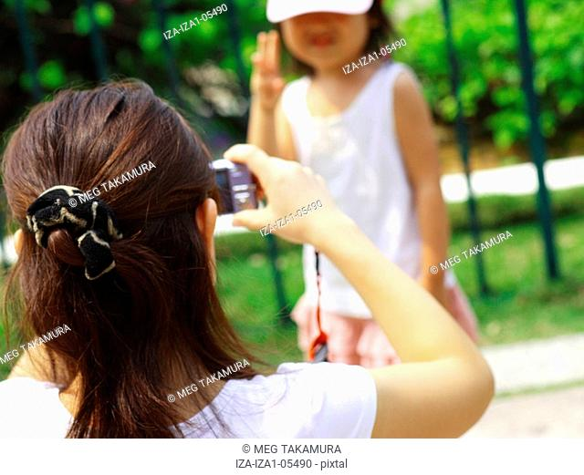Rear view of a young woman taking a picture of her daughter
