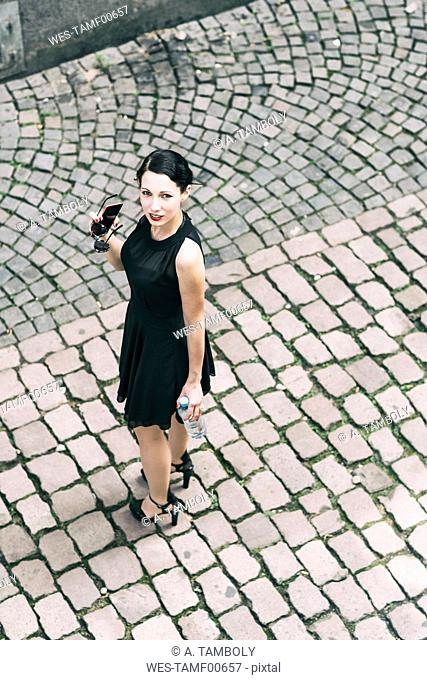 Young woman standing on cobblestones wearing black dress