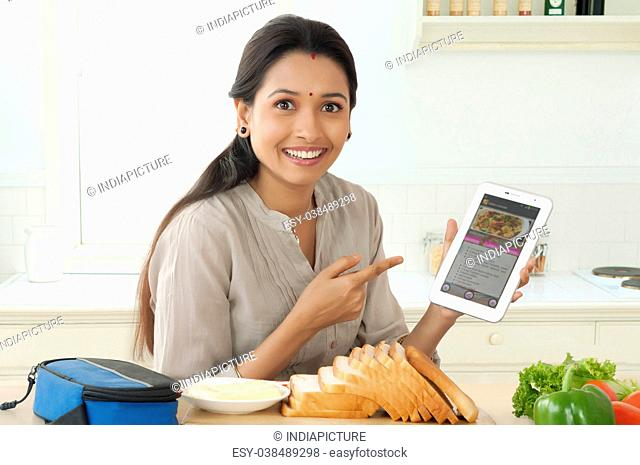 Mother pointing recipe in tablet device