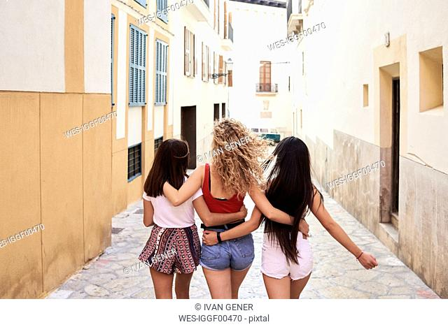 Spain, Mallorca, Palma, rear view of three young women walking in the city embracing each other