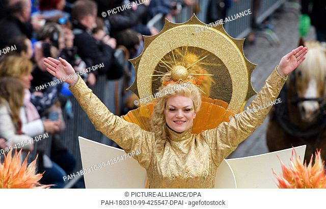 10 March 2018, Germany, Eisenach: 'Frau Sunna' sits on a wagon at the 'Eisenacher Sommergewinn' parade, which celebrates the beginning of spring and is listed...