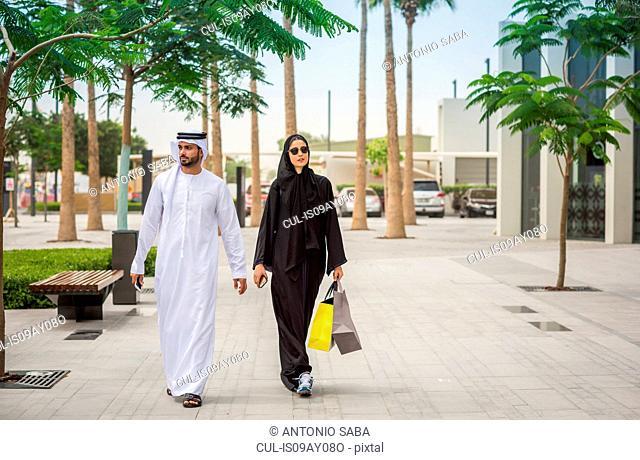 Middle eastern shopping couple wearing traditional clothing walking along street, Dubai, United Arab Emirates