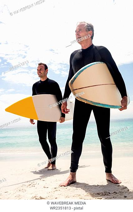 Father and son standing with surfboard and looking at a distance