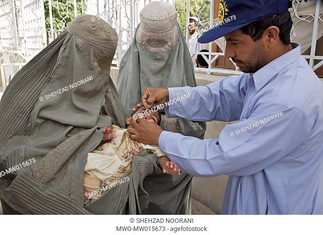 A health worker vaccinates an infant against polio, outside a Government building in Kandahar city, in Afghanistan June 18, 2007