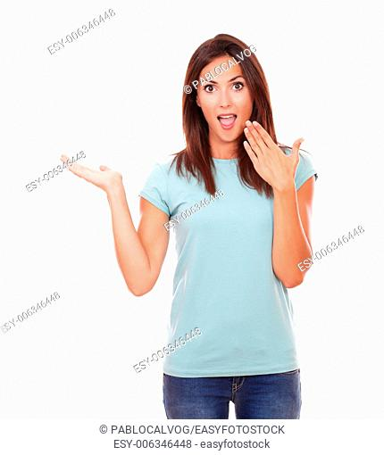 Portrait of surprised funny adult lady on blue t-shirt and blue jeans holding her right palm up while looking at you and standing on isolated white background -...