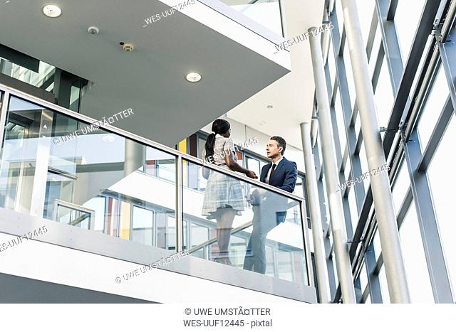 Businessman and woman talking on office floor
