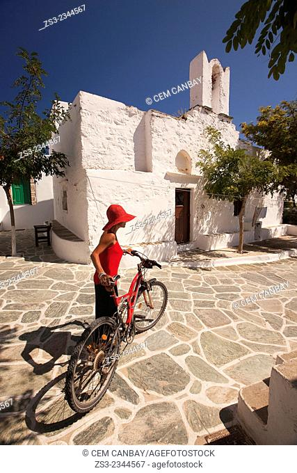 Woman holding a bike in front of an old church in Hora, Folegandros, Cyclades Islands, Greek Islands, Greece, Europe