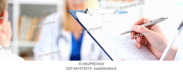 Female medicine doctor hand holding silver pen looking in clipboard pad closeup. Ward round patient visit check 911 medical calculation and statistics concept