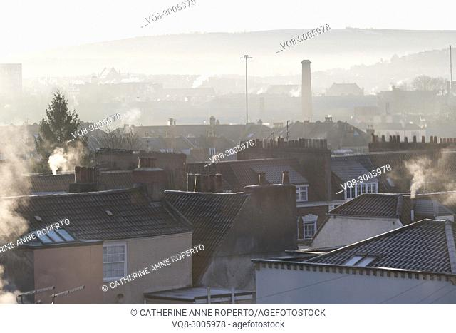Frosty rooftops, smoking chimneys and muted tones as the sun rises over the harbour in Hotwells, Bristol, England