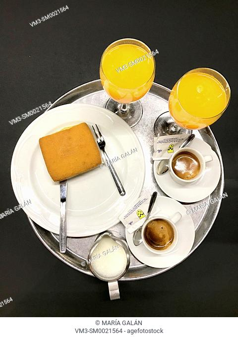 Two glasses of orange juice, two cups of coffee, milk and sobao on a tray. Spain