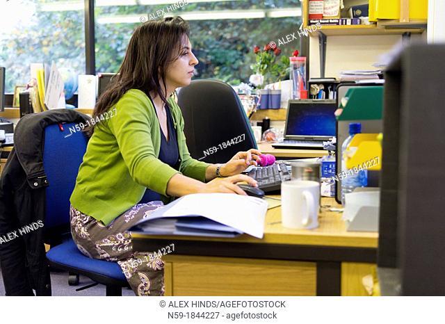 Female teacher working at her desk in staffroom