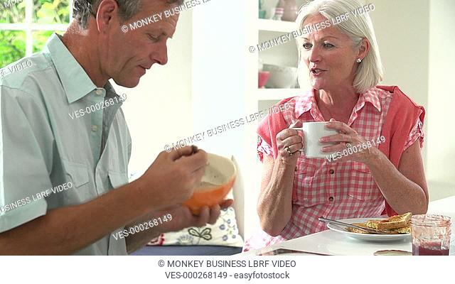 Middle aged couple talking together over breakfast. Shot on Sony FS700 in PAL format at a frame rate of 25fps