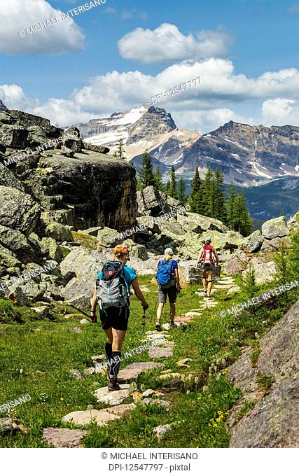 Three female hikers on rocky pathway in a mountain meadow with mountain, blue sky and clouds in the background; British Columbia, Canada