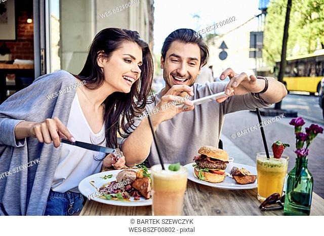 Happy young couple taking photo of food at outdoors restaurant
