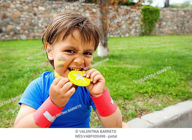 Little boy biting on medal