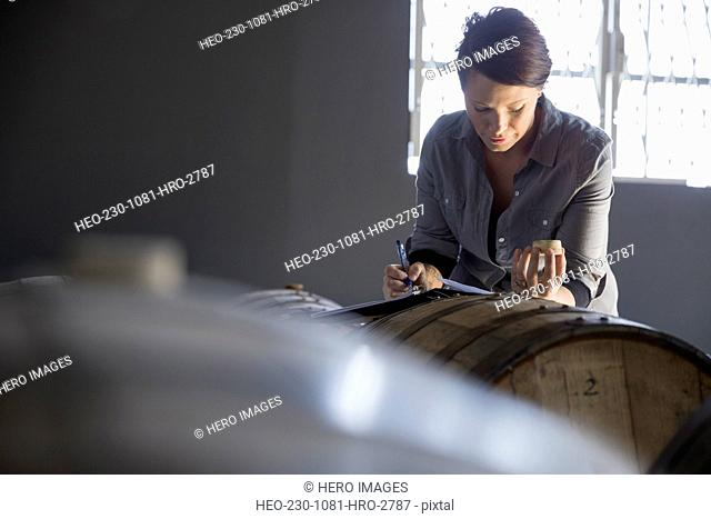 Brewery worker looking into beer barrel