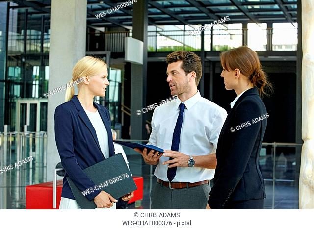 Three business colleagues discussing in office lobby