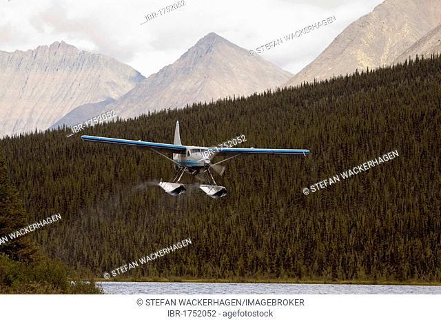 Bush plane, float plane de Havilland Canada DHC-3 Otter taking off from McClusky Lake, Wind River, Mackenzie Mountains, Yukon Territory, Canada