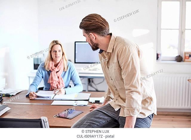 Man sitting on desk in office talking to colleague