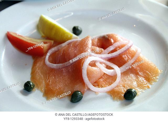 Smoked salmon on plate with onion lemon tomato and capers
