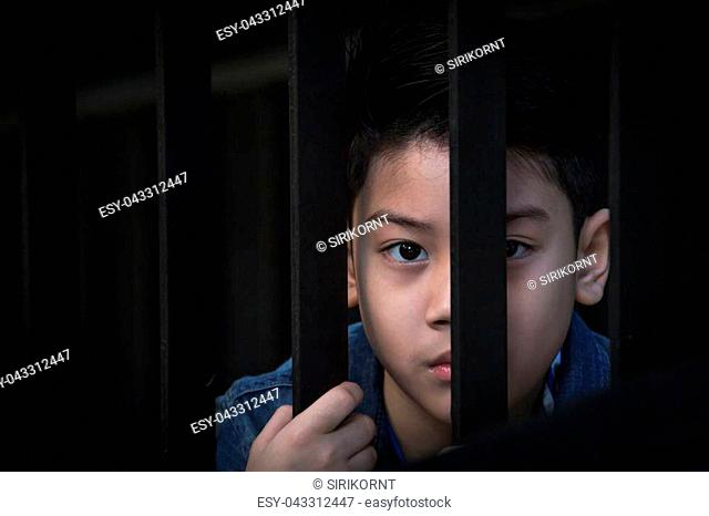 asian boy Hand in jail looking out the window