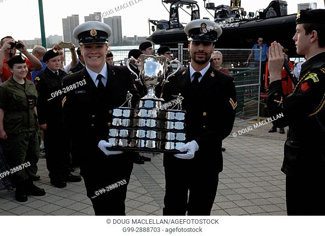 Two male officers happily carry the Memorial Cup trophy from a ship past a crowd of spectators and an honour guard