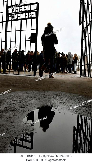 Visitors walk through the gate of the former Sachsenhausen concentration camp, which bears the words 'Arbeit macht frei' (work sets you free), in Oranienburg