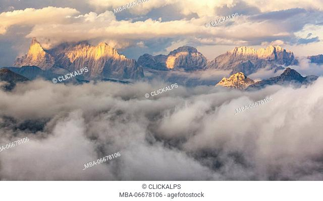 Europe, Italy, Veneto, Belluno. The sunset light on some dolomite's peak, surrounded by a sea of clouds, Dolomites