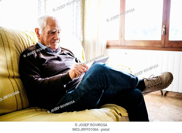 Senior man sitting on couch using tablet