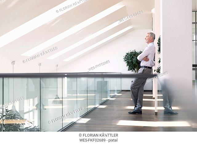 Businessman leaning against wall, smiling relaxed