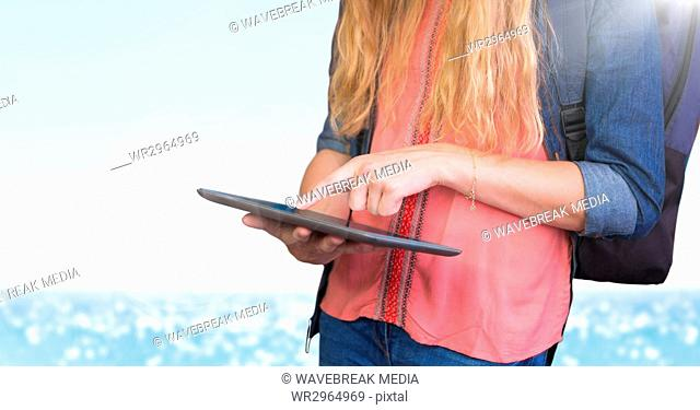 Woman mid section with backpack and tablet against blurry water and flare