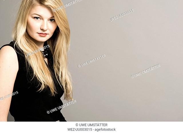Portrait of blond woman in front of grey background