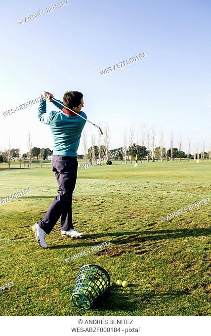 Golfer hitting a golf ball in the driving range of a golf club